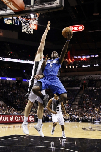 Oct 22, 2013; San Antonio, TX, USA; Orlando Magic guard Victor Oladipo (5) drives to the basket as San Antonio Spurs forward Aron Baynes (16) defends during the second half at AT&T Center. The Spurs won 123-101. Mandatory Credit: Soobum Im-USA TODAY Sports