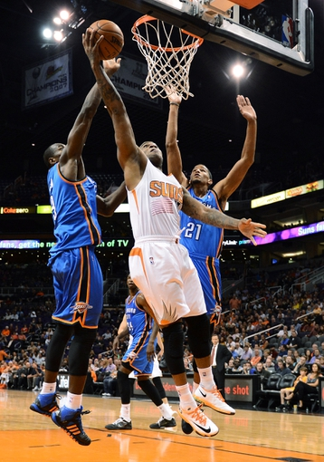 Oct 22, 2013; Phoenix, AZ, USA;Phoenix Suns forward P.J Tucker (17) lays up the ball against the Oklahoma City Thunder forward Serge Ibaka (9) and guard Andre Roberson (21) in the second half at US Airways Center. The Suns defeated the Thunder 88 to 76. Mandatory Credit: Jennifer Stewart-USA TODAY Sports
