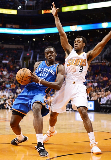 Oct 22, 2013; Phoenix, AZ, USA; Oklahoma City Thunder guard Thabo Sefolosha (25) drives the ball against defender Phoenix Suns guard Ish Smith (3) in the first half at US Airways Center. The Suns defeated the Thunder 88 to 76. Mandatory Credit: Jennifer Stewart-USA TODAY Sports