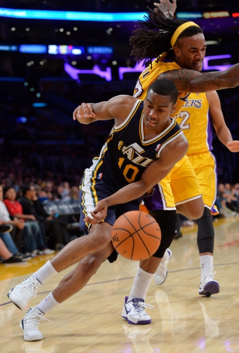Oct 22, 2013; Los Angeles, CA, USA; Utah Jazz point guard Alec Burks (10) is fouled by Los Angeles Lakers center Jordan Hill (27) as he tries to drive to the baseline during second half action at Staples Center. Mandatory Credit: Robert Hanashiro-USA TODAY Sports