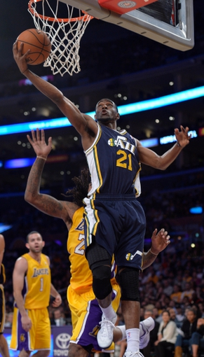 Oct 22, 2013; Los Angeles, CA, USA;  Utah Jazz shooting guard Ian Clark (21) scores past Los Angeles Lakers center Jordan Hill (27) during second half action at Staples Center. Mandatory Credit: Robert Hanashiro-USA TODAY Sports