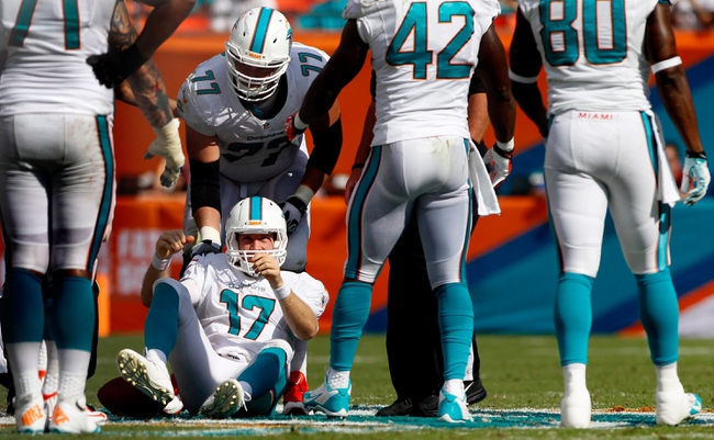 Oct 20, 2013; Miami Gardens, FL, USA;  Miami Dolphins tackle Will Yeatman (72) is helped to his feet by tackle Tyson Clabo (77) in the second half of a game against the Buffalo Bills at Sun Life Stadium. Mandatory Credit: Robert Mayer-USA TODAY Sports