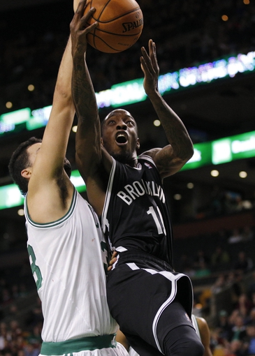 Oct 23, 2013; Boston, MA, USA; Brooklyn Nets point guard Tyshawn Taylor (10) drives the ball against Boston Celtics center Vitor Faverani (38) during the first quarter at TD Garden. Mandatory Credit: David Butler II-USA TODAY Sports