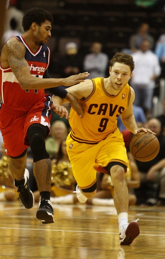 Oct 23, 2013; Cincinnati, OH, USA; Cleveland Cavaliers guard Matthew Dellavedova (9) drives down court against Washington Wizards guard Glen Rice Jr. (14) in the second half at US Bank Arena. Washington won 101-82. Mandatory Credit: David Kohl-USA TODAY Sports