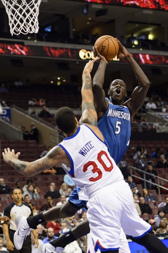 Oct 23, 2013; Philadelphia, PA, USA; Minnesota Timberwolves center Gorgui Dieng (5) shoots under pressure from Philadelphia 76ers forward Royce White (30) during the fourth quarter at Wells Fargo Center. The Timberwolves defeated the Sixers 125-102. Mandatory Credit: Howard Smith-USA TODAY Sports