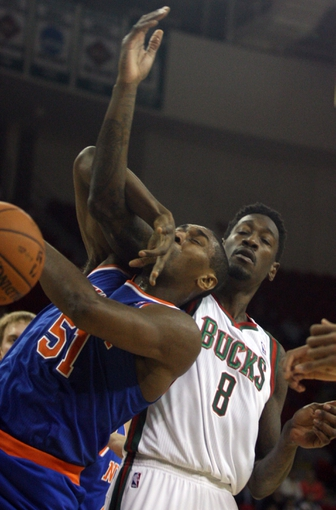 Oct 23, 2013; Green Bay, WI, USA; New York Knicks forward World Peace (51) gets tangled up with Milwaukee Bucks center Larry Sanders (8) at the Resch Center in Green Bay.  The Milwaukee Bucks defeated the New York Knicks 105-95. Mandatory Credit: Mary Langenfeld-USA TODAY SportsLangenfeld-USA TODAY Sports