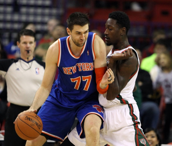 Oct 23, 2013; Green Bay, WI, USA; New York Knicks forward Andrea Bargnani (77) attempts to move the ball around Milwaukee Bucks center Larry Sanders (right) at the Resch Center in Green Bay.  The Milwaukee Bucks defeated the New York Knicks 105-95. Mandatory Credit: Mary Langenfeld-USA TODAY Sports