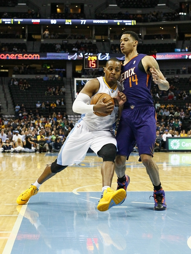 Oct 23, 2013; Denver, CO, USA; Phoenix Suns shooting guard Gerald Green (14) guards Denver Nuggets point guard Randy Foye (4) in the fourth quarter at the Pepsi Center. The Suns won 98-79. Mandatory Credit: Isaiah J. Downing-USA TODAY Sports