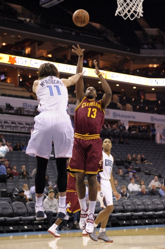 Oct 24, 2013; Charlotte, NC, USA; Cleveland Cavaliers forward center Tristan Thompson (13) shoots as he is defended by Charlotte Bobcats forward Josh McRoberts (1) at Time Warner Cable Arena. Mandatory Credit: Sam Sharpe-USA TODAY Sports