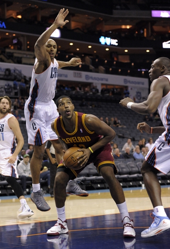 Oct 24, 2013; Charlotte, NC, USA; Cleveland Cavaliers forward center Tristan Thompson (13) looks to shoot as he is blocked by Charlotte Bobcats guard Gerald Henderson (9) at Time Warner Cable Arena. Mandatory Credit: Sam Sharpe-USA TODAY Sports