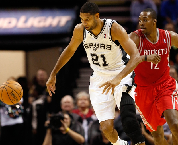 Oct 24, 2013; San Antonio, TX, USA; San Antonio Spurs forward Tim Duncan (21) and Houston Rockets center Dwight Howard (12) chase a loose ball during the first half at AT&T Center. Mandatory Credit: Soobum Im-USA TODAY Sports