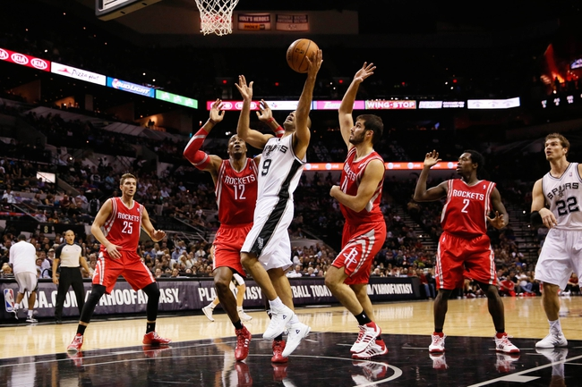 Oct 24, 2013; San Antonio, TX, USA; San Antonio Spurs guard Tony Parker (9) drives to the basket as Houston Rockets center Dwight Howard (12) and forward Omri Casspi (18)  defends during the first half at AT&T Center. Mandatory Credit: Soobum Im-USA TODAY Sports