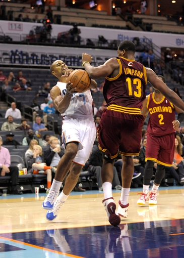 Oct 24, 2013; Charlotte, NC, USA; Charlotte Bobcats guard Ramon Sessions (7) gets fouled by Cleveland Cavaliers forward center Tristan Thompson (13) during the game at Time Warner Cable Arena. The Bobcats won 102-95. Mandatory Credit: Sam Sharpe-USA TODAY Sports