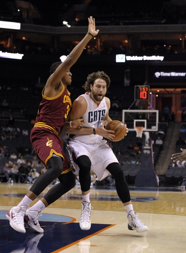 Oct 24, 2013; Charlotte, NC, USA; Charlotte Bobcats forward Josh McRoberts (11) drives past Cleveland Cavaliers guard forward Carrick Felix (30) during the game at Time Warner Cable Arena. Bobcats win 102-95. Mandatory Credit: Sam Sharpe-USA TODAY Sports