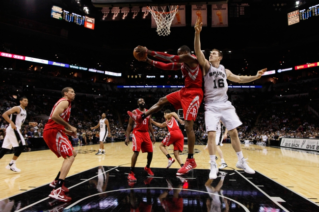 Oct 24, 2013; San Antonio, TX, USA; Houston Rockets center Dwight Howard (12) pulls down a rebound against San Antonio Spurs forward Aron Baynes (16) during the second half at AT&T Center. The Rockets won 109-92. Mandatory Credit: Soobum Im-USA TODAY Sports