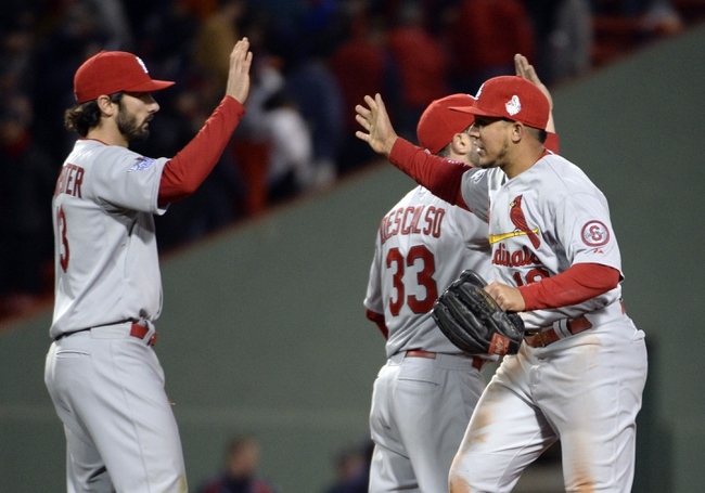 Oct 24, 2013; Boston, MA, USA; St. Louis Cardinals players Matt Carpenter (13) , Jon Jay (19) and Daniel Descalso (33) celebrate on the field after game two of the MLB baseball World Series against the Boston Red Sox at Fenway Park. Mandatory Credit: Robert Deutsch-USA TODAY Sports