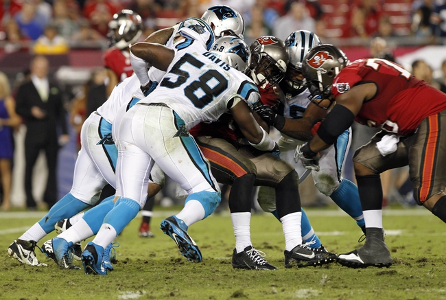 Oct 24, 2013; Tampa, FL, USA; Tampa Bay Buccaneers running back Mike James (25) is tackled by Carolina Panthers outside linebacker Thomas Davis (58) and teammates during the second half at Raymond James Stadium. Carolina Panthers defeated the Tampa Bay Buccaneers 31-13. Mandatory Credit: Kim Klement-USA TODAY Sports