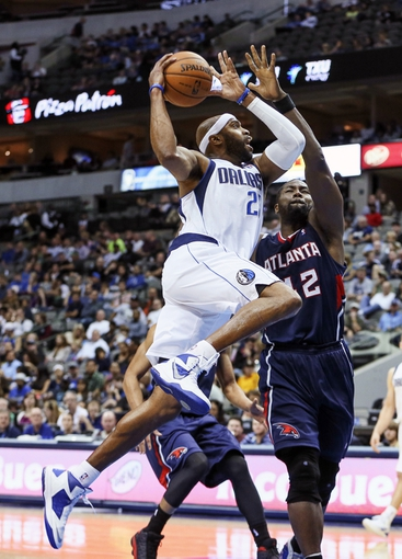 Oct 23, 2013; Dallas, TX, USA; Dallas Mavericks shooting guard Vince Carter (25) shoots over Atlanta Hawks power forward Elton Brand (42) during the game at American Airlines Center. Dallas won 99-88. Mandatory Credit: Kevin Jairaj-USA TODAY Sports