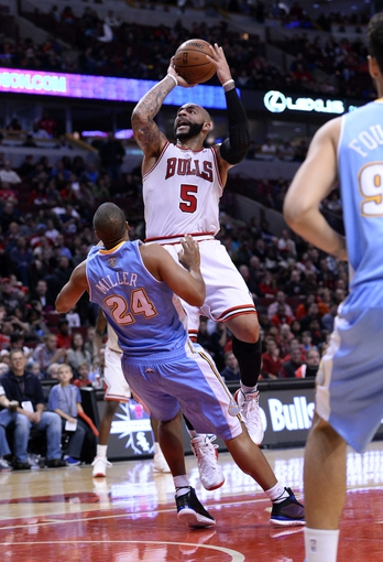 Oct 25, 2013; Chicago, IL, USA; Chicago Bulls power forward Carlos Boozer (5) shoots the ball against Denver Nuggets point guard Andre Miller (24) during the second half at the United Center. Chicago defeats Denver 94-89. Mandatory Credit: Mike DiNovo-USA TODAY Sports