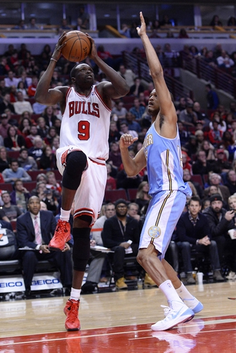 Oct 25, 2013; Chicago, IL, USA;  Chicago Bulls small forward Luol Deng (9) shoots the ball against Denver Nuggets power forward Anthony Randolph (15) during the second half at the United Center. Chicago defeats Denver 94-89. Mandatory Credit: Mike DiNovo-USA TODAY Sports