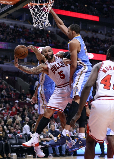 Oct 25, 2013; Chicago, IL, USA; Chicago Bulls power forward Carlos Boozer (5) is fouled by Denver Nuggets center JaVale McGee (34) during the second half at the United Center. Chicago defeats Denver 94-89. Mandatory Credit: Mike DiNovo-USA TODAY Sports