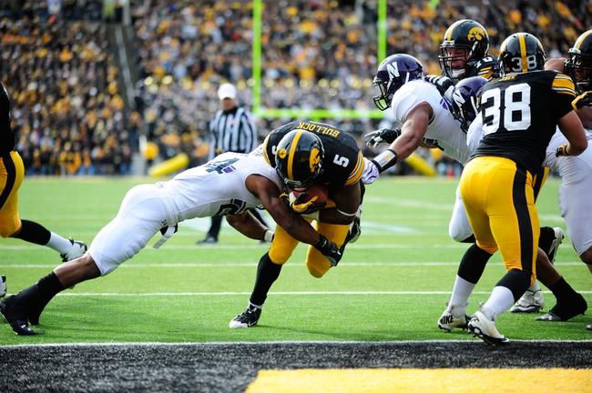 Oct 26, 2013; Iowa City, IA, USA; Iowa Hawkeyes running back Damon Bullock (5) scores on a three-yard touchdown run in the first quarter at Kinnick Stadium. Mandatory Credit: Byron Hetzler-USA TODAY Sports