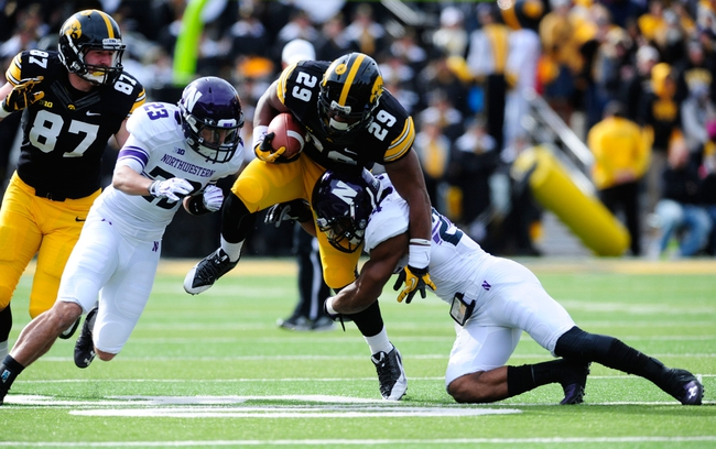 Oct 26, 2013; Iowa City, IA, USA; Iowa Hawkeyes running back LeShun Daniels (29) is tackled by Northwestern Wildcats cornerback Nick VanHoose (23) and safety Ibraheim Campbell (24)in the first quarter at Kinnick Stadium. Mandatory Credit: Byron Hetzler-USA TODAY Sports