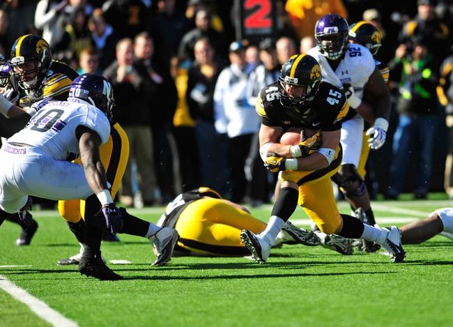 Oct 26, 2013; Iowa City, IA, USA; Iowa Hawkeyes fullback Mark Weisman (45) rushes as Northwestern Wildcats safety Traveon Henry (10) defends during overtime at Kinnick Stadium. Iowa won 17-10. Mandatory Credit: Byron Hetzler-USA TODAY Sports
