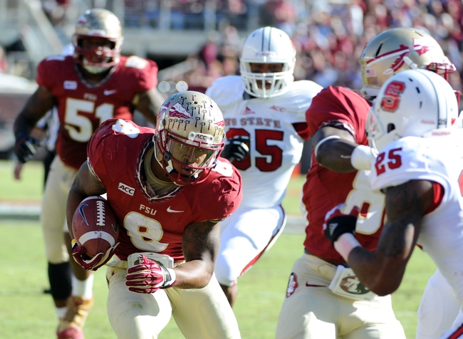 Oct 26, 2013; Tallahassee, FL, USA; Florida State Seminoles running back Devonta Freeman (8) runs the ball for a touchdown during the first quarter of the game against the North Carolina State Wolfpack at Doak Campbell Stadium. Mandatory Credit: Melina Vastola-USA TODAY Sports