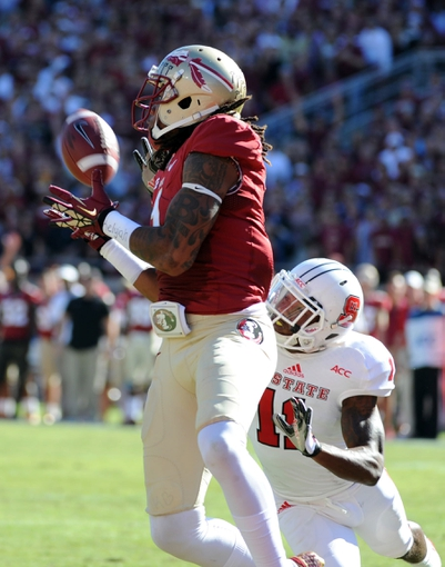 Oct 26, 2013; Tallahassee, FL, USA; Florida State Seminoles wide receiver Kelvin Benjamin (1) catches a pass for a touchdown past North Carolina State Wolfpack cornerback Juston Burris (11) during the first quarter of the game at Doak Campbell Stadium. Mandatory Credit: Melina Vastola-USA TODAY Sports
