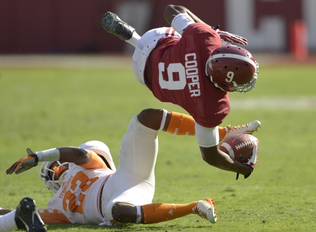 Oct 26, 2013; Tuscaloosa, AL, USA; Alabama Crimson Tide wide receiver Amari Cooper (9) gets tripped up by Tennessee Volunteers defensive back Malik Foreman (22) during the first quarter at Bryant-Denny Stadium. Mandatory Credit: John David Mercer-USA TODAY Sports