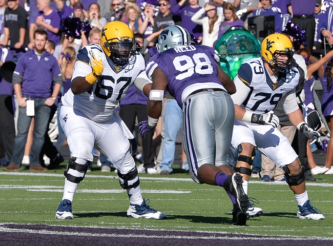 Oct 26, 2013; Manhattan, KS, USA; West Virginia Mountaineers offensive linesman Quinton Spain (67) blocks Kansas State Wildcats defensive lineman Chaquil Reed (98) during the first half at Bill Snyder Family Stadium. Mandatory Credit: Jasen Vinlove-USA TODAY Sports