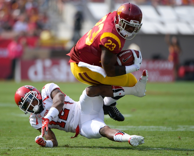 Oct 26, 2013; Los Angeles, CA, USA; Utah Utes defensive back Justin Thomas (12) trips up USC Trojans running back Tre Madden (23) for no gain during second quarter action at Los Angeles Memorial Coliseum. Mandatory Credit: Robert Hanashiro-USA TODAY Sports