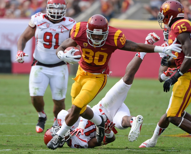 Oct 26, 2013; Los Angeles, CA, USA;  USC Trojans wide receiver De'Von Flournoy (80) breaks a tackle by Utah Utes defensive back Eric Rowe (18) to gain extra yards during second quarter action at Los Angeles Memorial Coliseum. Mandatory Credit: Robert Hanashiro-USA TODAY Sports