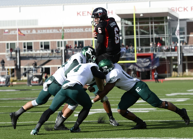 Oct 26, 2013; DeKalb, IL, USA; Northern Illinois Huskies quarterback Jordan Lynch (6) leaps into the end zone against Eastern Michigan Eagles defensive back Willie Creear (4) and linebacker Great Ibe (10) during the first half at Huskie Stadium. Mandatory Credit: Mike DiNovo-USA TODAY Sports