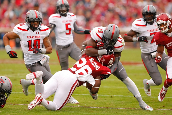 Oct 26, 2013; Norman, OK, USA; Texas Tech Red Raiders line backer Sam Eguavoen (13) tackles Oklahoma Sooners Damien Williams (26) during the first quarter at Gaylord Family - Oklahoma Memorial Stadium. Mandatory Credit: Alonzo Adams-USA TODAY Sports