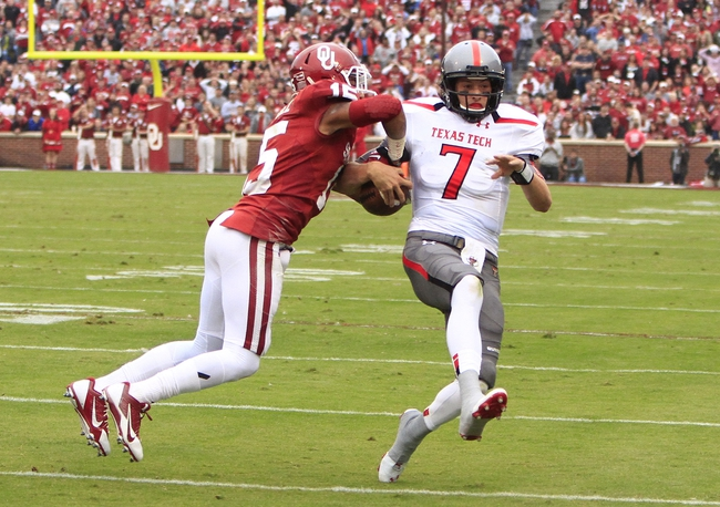 Oct 26, 2013; Norman, OK, USA; Texas Tech Red Raiders quarterback Davis Webb (7) attempts to break a tackle by Oklahoma Sooners Zach Sanchez (15) during the first quarter at Gaylord Family-Oklahoma Memorial Stadium. Mandatory Credit: Alonzo Adams-USA TODAY Sports