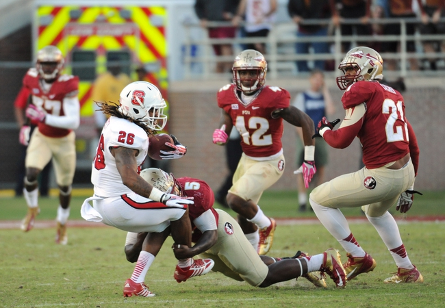Oct 26, 2013; Tallahassee, FL, USA; North Carolina State Wolfpack running back Tony Creecy (26) is tackled by Florida State Seminoles linebacker Reggie Northrup (5) during the second half of the game at Doak Campbell Stadium. Mandatory Credit: Melina Vastola-USA TODAY Sports