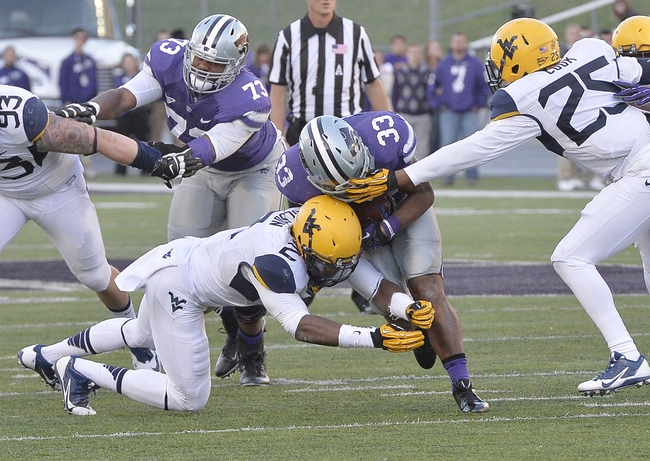 Oct 26, 2013; Manhattan, KS, USA; Kansas State Wildcats running back John Hubert (33) is tackled by West Virginia Mountaineers linebacker Brandon Golson (2) during the second half at Bill Snyder Family Stadium. The Wildcats defeat the Mountaineers 35-12. Mandatory Credit: Jasen Vinlove-USA TODAY Sports