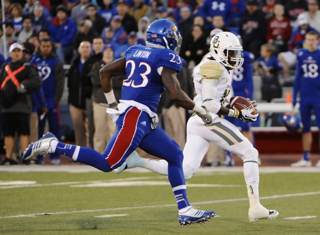 Oct 26, 2013; Lawrence, KS, USA; Baylor Bears wide receiver Tevin Reese (16) runs for a touchdown after a catch against Kansas Jayhawks safety Dexter Linton (23) in the first half at Memorial Stadium. Mandatory Credit: John Rieger-USA TODAY Sports