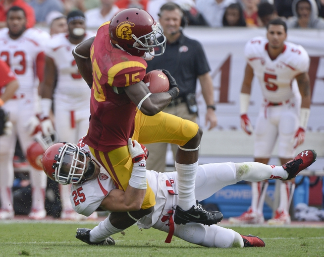 Oct 26, 2013; Los Angeles, CA, USA; Utah Utes defensive back Mike Honeycutt (25) tries to bring down USC Trojans wide receiver Nelson Agholor (15) during second half action at Los Angeles Memorial Coliseum. The Trojans went on to a 19-3 win.  Mandatory Credit: Robert Hanashiro-USA TODAY Sports