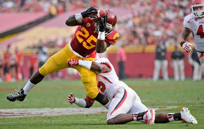 Oct 26, 2013; Los Angeles, CA, USA;  USC Trojans running back Silas Redd (25) hauls in a pass as he is hit by Utah Utes defensive back Michael Walker (15) during second half action at Los Angeles Memorial Coliseum. The Trojans went on to a 19-3 win. Mandatory Credit: Robert Hanashiro-USA TODAY Sports