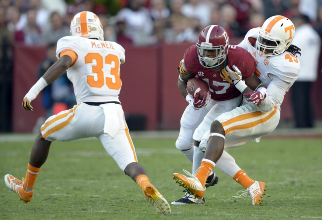 Oct 26, 2013; Tuscaloosa, AL, USA; Alabama Crimson Tide running back Kenyan Drake (17) carries for more yards as Tennessee Volunteers linebacker A.J. Johnson (45) tries to tackle during the fourth quarter at Bryant-Denny Stadium. Mandatory Credit: John David Mercer-USA TODAY Sports
