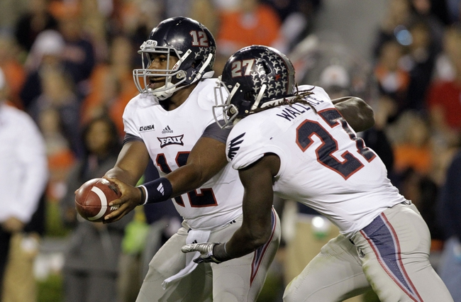 Oct 26, 2013; Auburn, AL, USA; Florida Atlantic Owls quarterback Jaquez Johnson (12) hands off to running back Jonathan Wallace (27) during the first half against the Auburn Tigers at Jordan Hare Stadium. Mandatory Credit: John Reed-USA TODAY Sports
