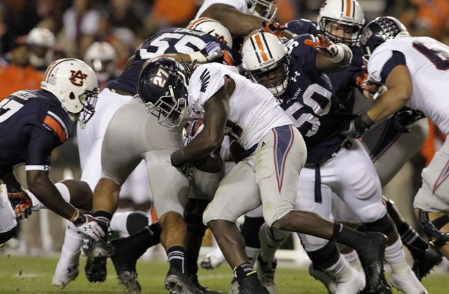Oct 26, 2013; Auburn, AL, USA; Florida Atlantic Owls running back Jonathan Wallace (27) is tackled by Auburn Tigers tackle Ben Bradley (50) and defensive back Robenson Therezie (27) during the first half at Jordan Hare Stadium. Mandatory Credit: John Reed-USA TODAY Sports