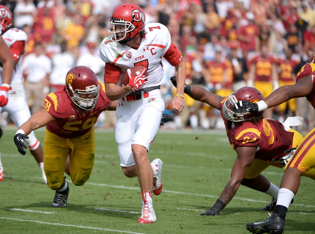 Oct 26, 2013; Los Angeles, CA, USA;  Utah Utes quarterback Travis Wilson (7) tries to run past  USC Trojans linebacker Kyle Yatabe (59) and USC Trojans defensive tackle Antwaun Woods (99) during second quarter at Los Angeles Memorial Coliseum. The Trojans won 19-3. Mandatory Credit: Robert Hanashiro-USA TODAY Sports