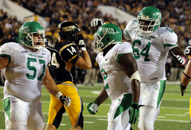 Oct 26, 2013; Hattiesburg, MS, USA; North Texas Mean Green running back Reggie Pegram (2) celebrates a touchdown run with teammates Mason Y'Barbo (57) and LaChris Anyiam (64) in the first quarter of their game against the Southern Miss Golden Eagles at M.M. Roberts Stadium. Mandatory Credit: Chuck Cook-USA TODAY Sports