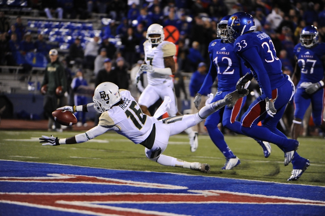 Oct 26, 2013; Lawrence, KS, USA; Baylor Bears wide receiver Tevin Reese (16) dives in for a touchdown against Kansas Jayhawks linebacker Cassius Sendish (33) and  cornerback Dexter McDonald (12) in the first half at Memorial Stadium. Mandatory Credit: John Rieger-USA TODAY Sports