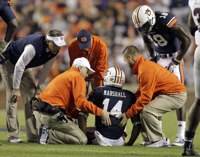 Oct 26, 2013; Auburn, AL, USA; Auburn Tigers head coach Gus Malzahn (left) looks on as the medical staff attends to quarterback Nick Marshall (14) during the first half against the Florida Atlantic Owls at Jordan Hare Stadium. Mandatory Credit: John Reed-USA TODAY Sports