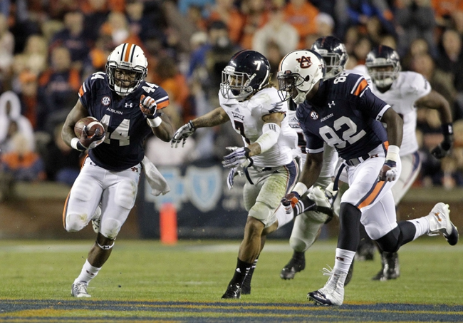 Oct 26, 2013; Auburn, AL, USA; Auburn Tigers running back Cameron Artis-Payne (44) gets past Florida Atlantic Owls defensive back Cre'von LeBlanc (7) during the first half at Jordan Hare Stadium. Mandatory Credit: John Reed-USA TODAY Sports